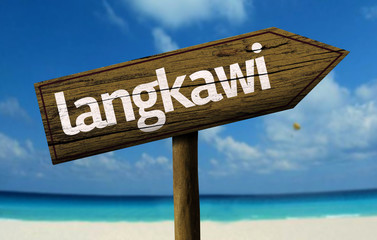 Langkawi wooden sign with a beach on background