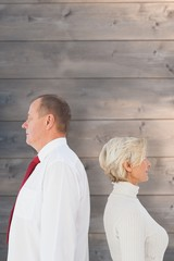 Composite image of older couple standing not facing each other