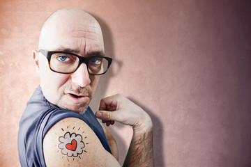 Funny Latin Lover shows his tattoo, pink background