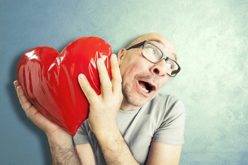 Man in love holds a red heart shape pillow