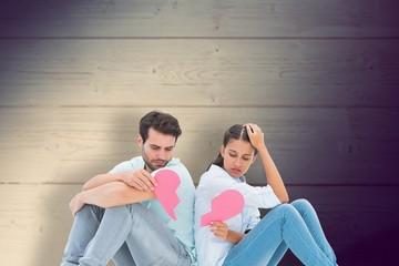 Sad couple sitting holding two halves of broken heart
