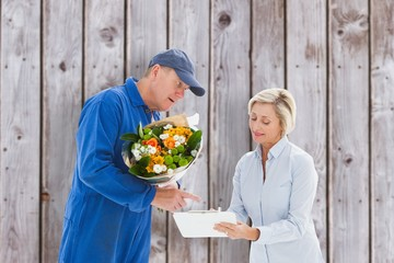 Composite image of happy flower delivery man with customer