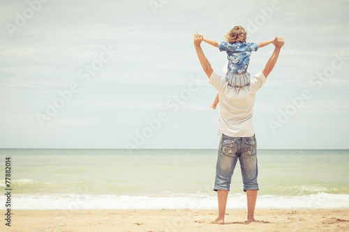 Father and son playing on the beach at the day time. - 77882014