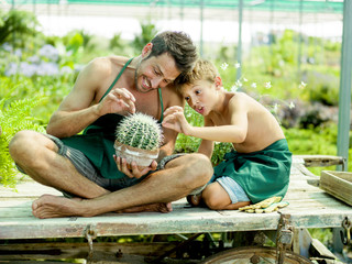 Young boy playing with his father in a green house