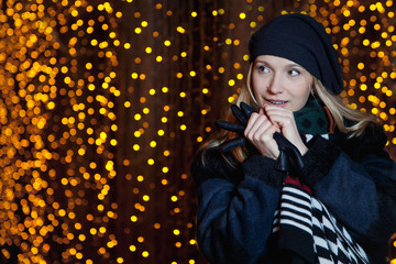 Beautiful blonde girl on blurred background of yellow lights
