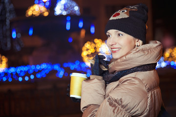 Smiling blonde girl standing on background with lights on the st