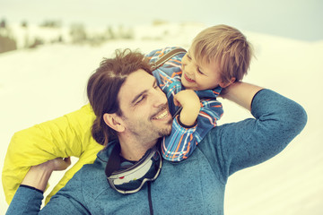 father lifting his son affectionately in the snow
