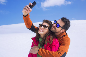 couple having a selfie on the snow