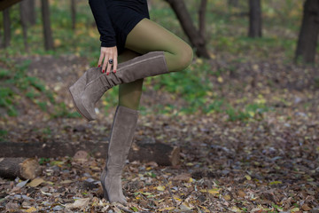 Beautiful woman legs in suede boots in autumn forest