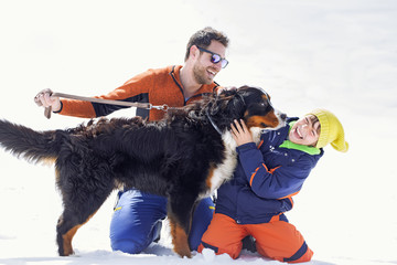 father, son and their dog having fun in the snow