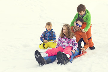 Father having fun in the snow with his children