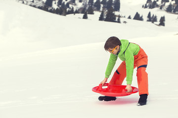 Young boy ready to sledding in the snow
