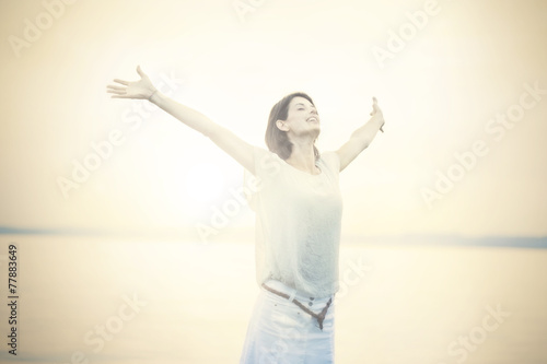 beautifull woman taking a deep breath at the sunset - 77883649