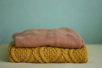 Ocher winter sweaters with green background, selective focus.