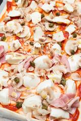 homemade pizza with ham,mozzarella,tomato sauce and capers