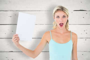 Composite image of shocked blonde holding a sheet of paper