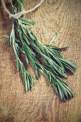 toning effect sprigs of rosemary on a wooden board closeup horiz