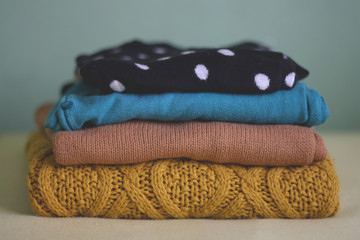 Pile of colorful winter sweaters, selective focus.
