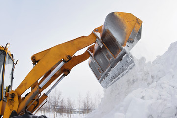 The bulldozer clears away snow drifts
