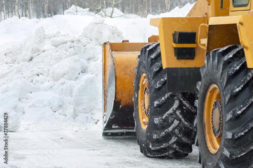 Leinwandbild Motiv The bulldozer cleans the road after a blizzard