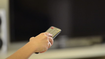 Person holding a remote control watching TV and changing channel