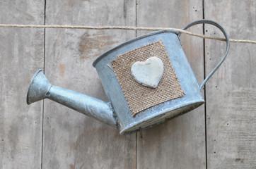 cœur sur arrosoir suspendu à un fil