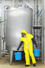 technician in protective uniform with  buckets at process tank