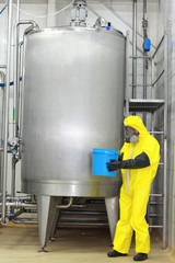 technician in protective uniform with bucket  at process tank