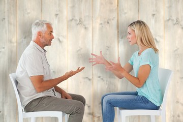 Unhappy couple sitting on chairs having an argument