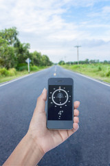 hand hold compass on smart phone on road
