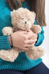 Girl holding teddybear, closeup