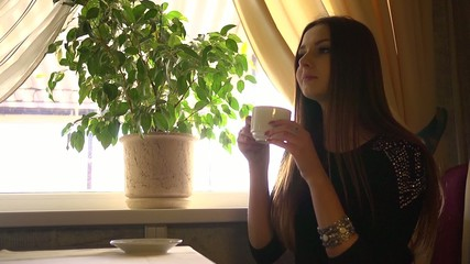 young beautiful girl drinking tea in the restaurant