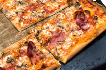Pizza con prosciutto, funghi, mozzarella e sugo
