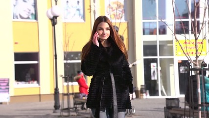 Young lovely girl walking talking on the phone
