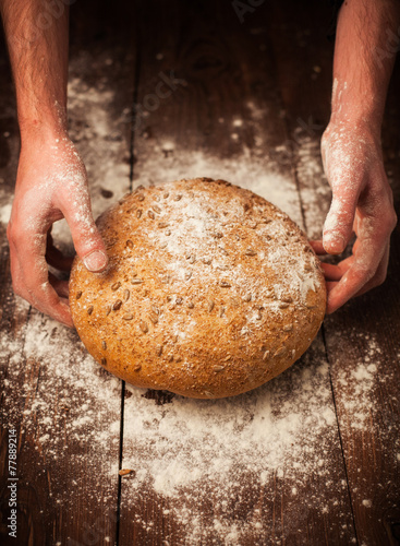 Fotobehang Brood Baker hands with fresh bread on table