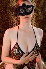 Frau in Erotik Kostüm trägt Maske