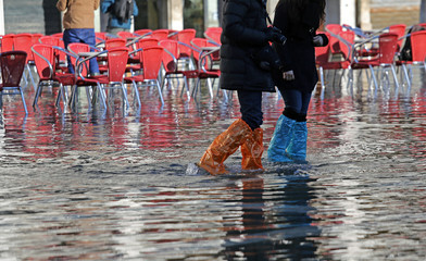 people with leggings and boots at high tide in Venice