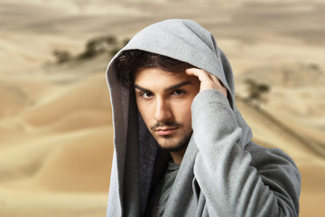 Man in gray cowl neck hoodie, desert landscape background
