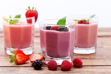 Drink smoothies summer strawberry, blackberry on wooden table.