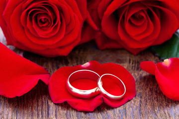 Wedding rings and wedding bouquet of red roses petals.