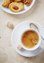 Cup of espresso with brown sugar and cookies