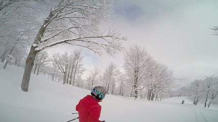 Kid skiing in powder snow in a mountain forest. winter day.