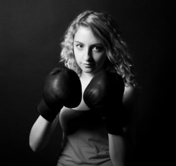 Woman boxer, model poses on the black background.