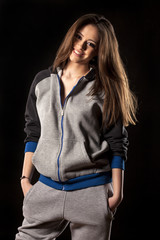 happy young woman in track suits on dark background