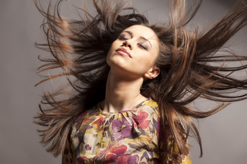 pretty girl with wind in her hair posing in the studio