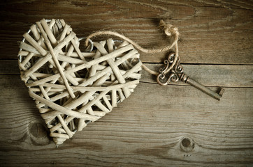 wicker heart handmade with the key lying on a wooden base . top