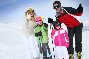Cheerful family at ski resort showing thumbs up