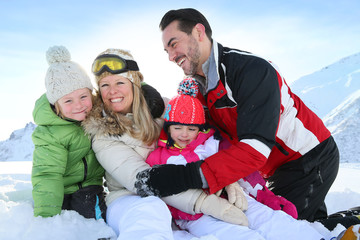 Cheerful family sitting in snow