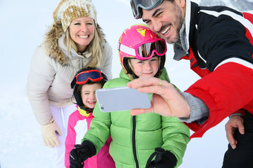 Family taking picture at the top of ski slope