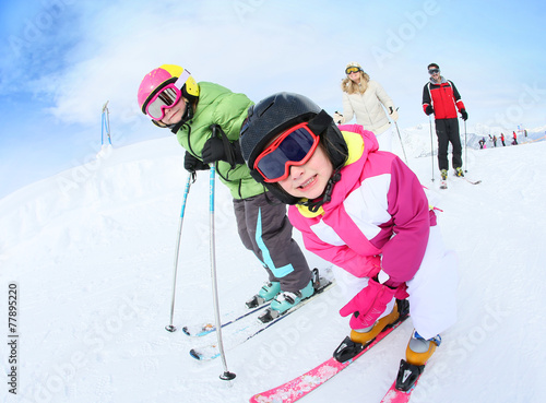 Staande foto Wintersporten Young girl learning how to ski with family